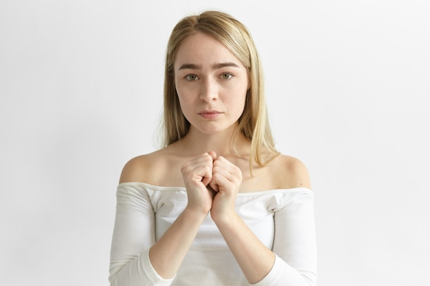 Human facial expressions and body language. picture of stylish young caucasian female with loose blonde hair posing indoors, holding two clenched fists together, having uneasy deep in thoughts look