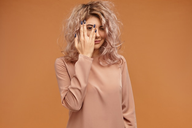 Human facial expressions and body language. portrait of fashionable hipster girl with messy pinkish hair and black long nails covering face