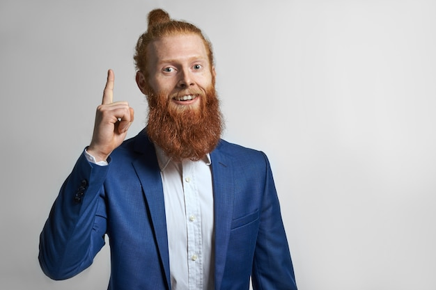 Human facial expressions and body language. studio shot of attractive fashionable successful young bearded male entrepreneur wearing elegant stylish suit, pointing index finger, having excited look
