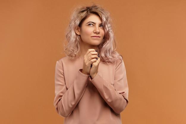 Выражения лица, эмоции и чувства человека. красивая стильная женщина-модельер с розовой прической смотрит вверх и кусает губы