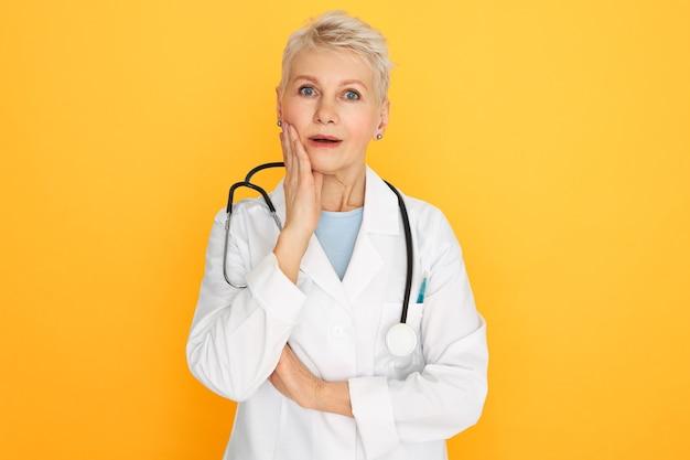人間の表情、感情、感情。感情的な驚きの引退した女性開業医が頬に手をつないで口を開け、既往歴や診断にショックを受けたスタジオ画像