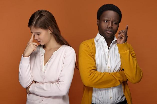 人間の表情、感情、感情。 2人の同僚が一緒に問題に取り組み、解決策を考えています。物思いにふける白人女性とポーズをとって、素晴らしいアイデアのサインとして指を上げるアフリカの男性