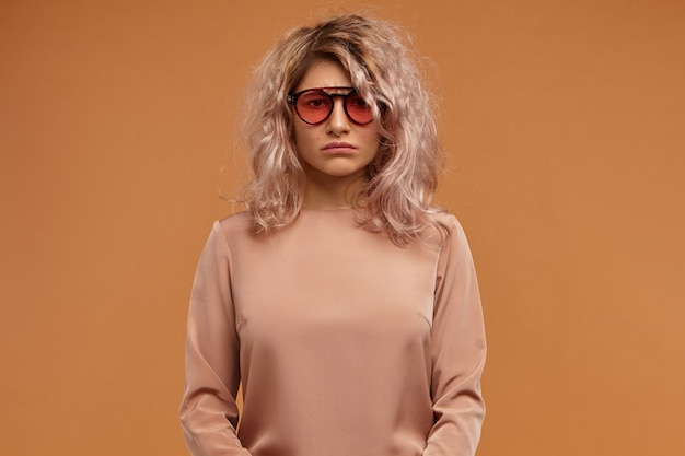 Espressioni facciali umane ed emozioni. giovane femmina sconvolta insoddisfatta che indossa occhiali da sole alla moda di cattivo umore, con sguardo annoiato