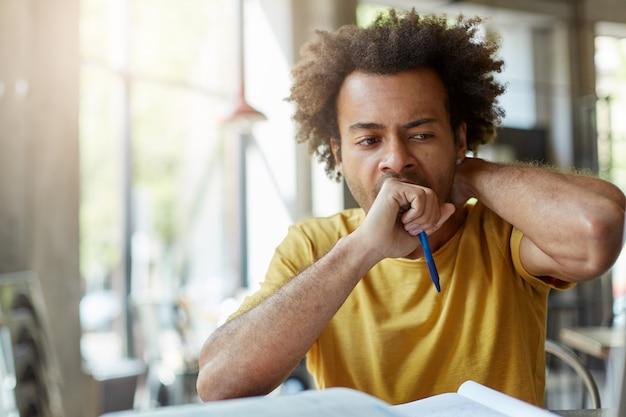 人間の顔の表情、感情、感情、態度。疲れて眠そうなアフロアメリカンの学生、あくびしながら口を拳で覆い、本を机に座って、試験の準備