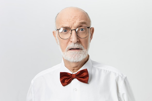 人間の表情、感情、感情、反応。ショックを受けた怖い顔をした眼鏡の魅力的な無精ひげを生やした引退した男。恐怖を表現するひげを生やしたヨーロッパの男性年金受給者