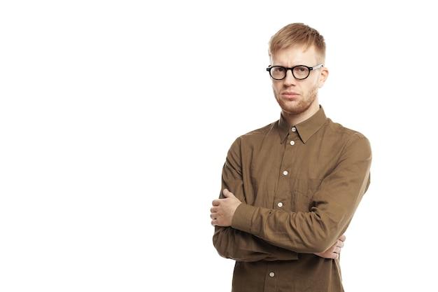 人間の表情、感情、感情、反応、態度、人生の知覚。しぶしぶ頑固な若い白人のひげを生やした男が腕を組んで真剣に見ている