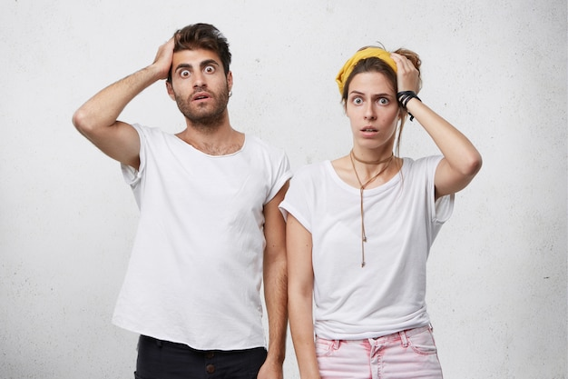 Human facial expressions, emotions, feelings, reaction and attitude. indoor shot of shocked forgetful young caucasian man and woman holding hands on heads and looking with shock and terror