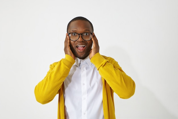 Human facial expressions, emotions, feelings, reaction and attitude. picture of handsome funny afro american man wearing stylish eyeglasses, opening mouth, being excited with positive good news