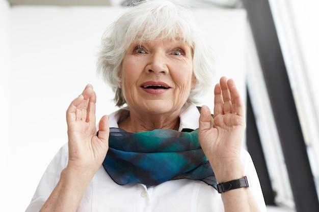 Espressioni facciali umane, emozioni, sentimenti e reazioni. immagine della signora caucasica invecchiata centrale elegante emotiva in vestiti alla moda che hanno stupito sguardo sorpreso, ricevendo notizie inaspettate