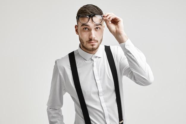 Espressioni facciali umane ed emozioni. il ritratto del giovane maschio caucasico barbuto alla moda emotivo si è vestito in abbigliamento formale che alza i suoi occhiali alla moda, avendo confuso lo sguardo interrogativo
