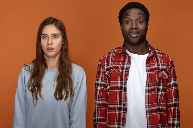 Human facial expressions, emotions, reaction and feelings. cute funny young interracial couple black guy and white female expressing amazement, opening their mouths, being surprised with news