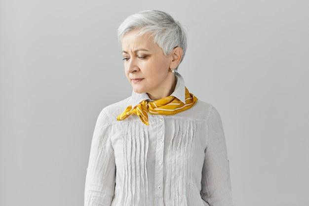 Espressioni facciali umane. accigliato dispiaciuto triste pensionato femmina con capelli grigi pixie che ha mal di testa, guardando in basso, in posa isolato al muro bianco con copyspace per il contenuto pubblicitario