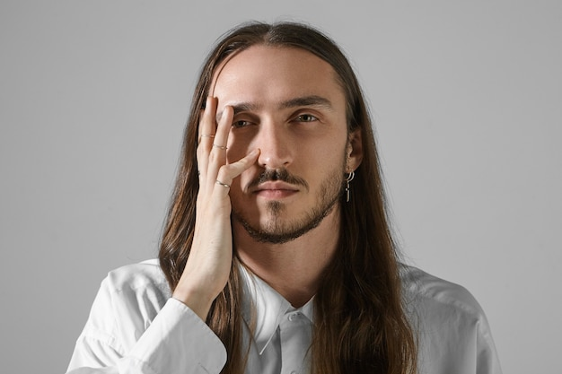 Выражения лица человека. изолированные выстрел красивый небритый молодой кавказский мужчина с длинными волосами позирует, серьезный взгляд, держа руку на лице, стильную рубашку и аксессуары