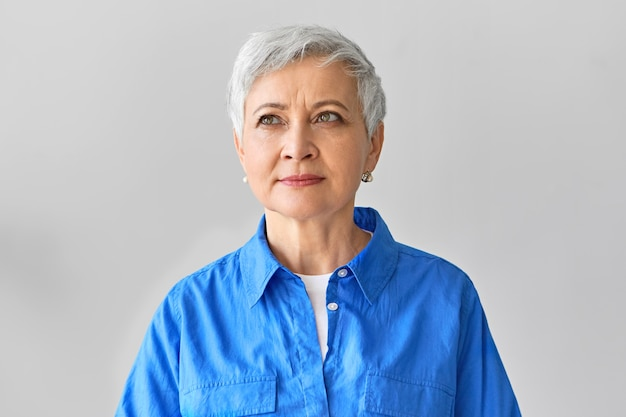 Human facial expressions. picture of thoughtful fashionable elegant european female designer with pixie haircut looking up with dreamy pensive smile, being inspired with sudden creative idea