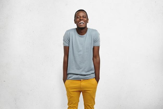 人間の感情と感情。ボディランゲージ。若い陽気なアフリカの男性、さりげなく服を着て、黄色のズボンのポケットに手、肩をすくめて、笑って、分離