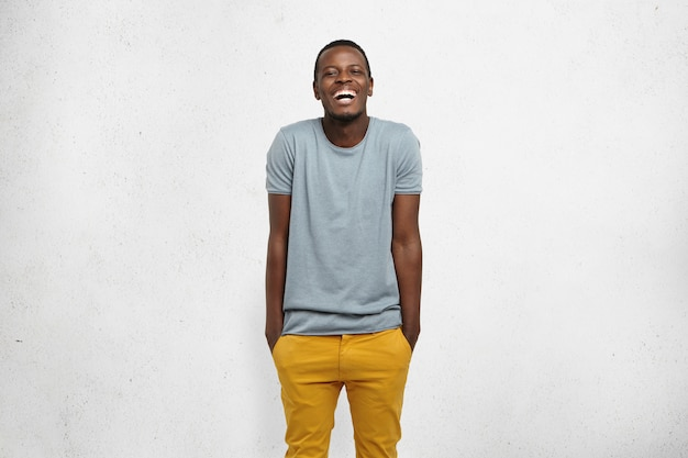 Human feelings and emotions. body language. young cheerful african male, dressed casually, hands in pockets of yellow pants, shrugging, laughing, isolated