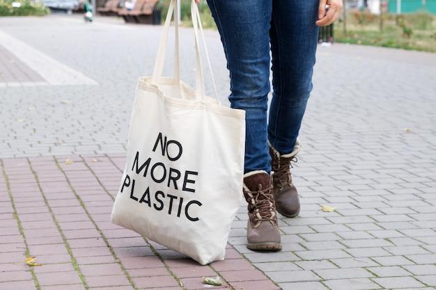 청바지와 부츠를 신은 인간의 발, 더 이상 플라스틱이 아닌 가방이 있는 가방