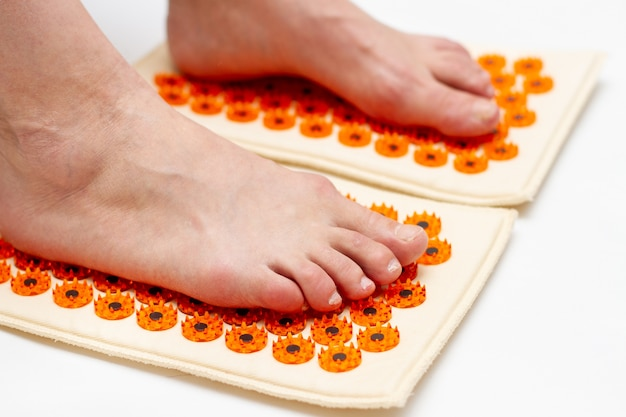 Human feet stand on acupuncture mat, close up