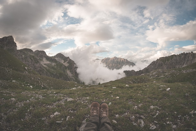 Human feet with hiking boots at the top of alpine valley with scenic clouds glowing at sunset. relax while looking at view. the alps