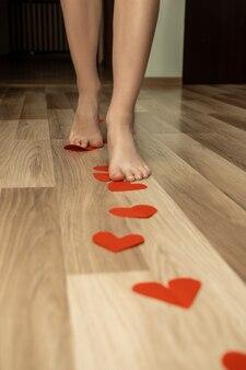인간의 여성 피트는 빨간 발렌타인 하트의 길을 따라 걸어. 집의 나무 바닥에 배치. 관계 개념. 놀라다.