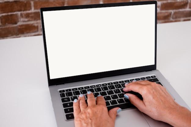 Человеческие женские руки, набрав на портативном компьютере. пустой экран, скопируйте пространство