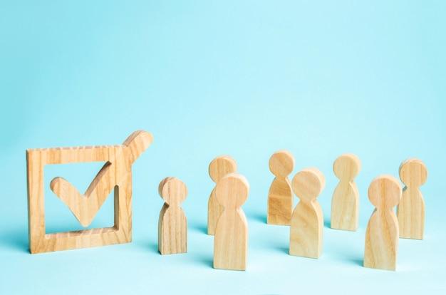 Человеческие фигуры стоят рядом с галочкой в коробке. концепция выборов