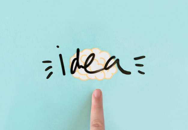 Human finger pointing at brain with idea word