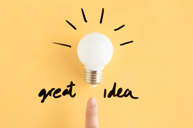 Human finger pointing towards light bulb with great idea text