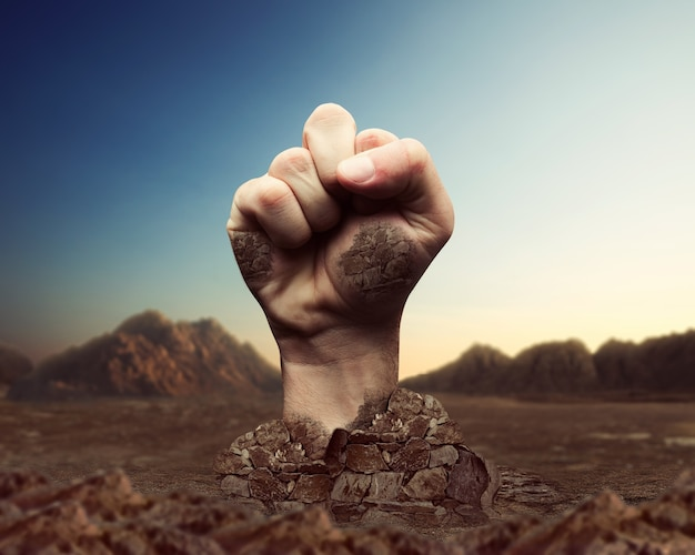 Human fist bursts through the ground over mountains background