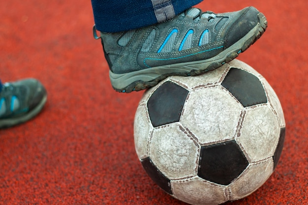 Human foot in a dirty sneaker on an old soccer ball.