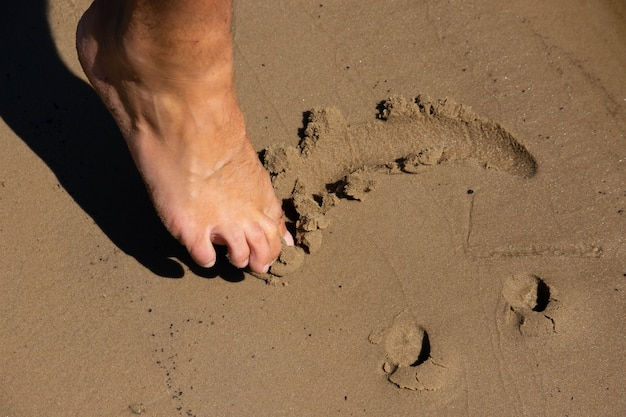 Human foot draws, smile in the sand. smile on the sand at the beach.