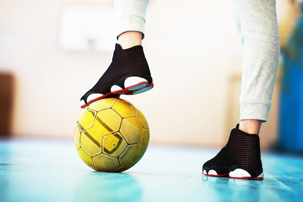 A human foot rest on the football on concrete floor. photo of one soccer ball and sneakers in a wooden floor.