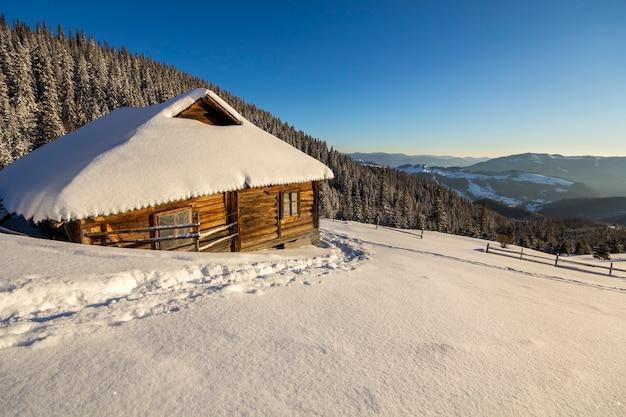 小さな古い木製の見捨てられた羊飼いにつながる白い深い雪の中の人間の足跡の道