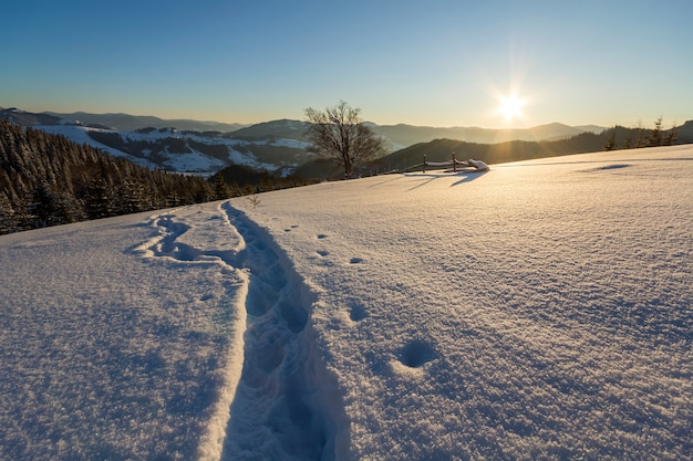 Human footprint track path in crystal white deep snow in empty field