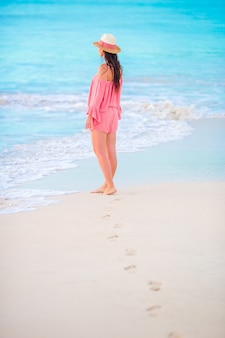 Человеческие следы на белом песчаном пляже на фоне красивой молодой женщины