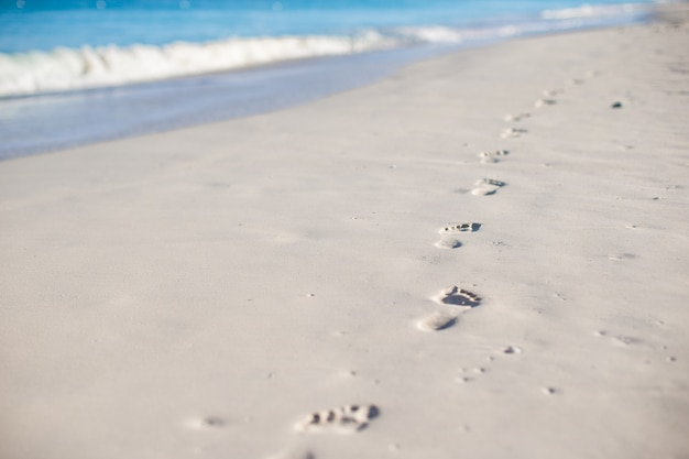 Human footprints on white sand beach