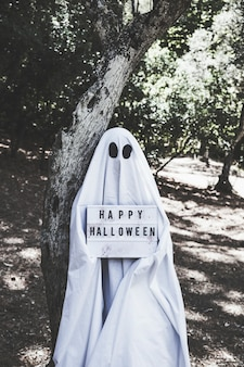 Human in ghost costume near tree in forest holding halloween tablet