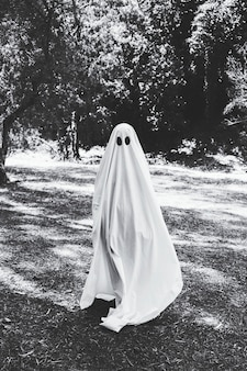 Human in ghost costume standing in forest