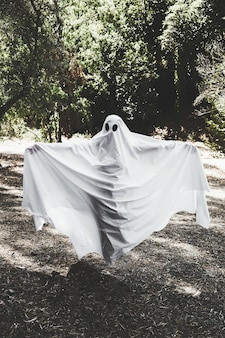 Human in ghost costume with upping hands in forest