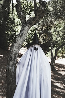 Human in ghost costume and wizard hat near tree in forest