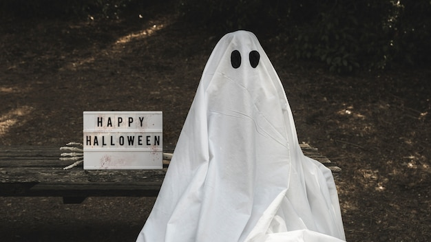 Human in ghost suit sitting on bench near halloween tablet