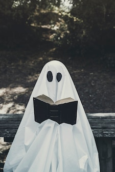 Human in ghost suit sitting on bench and reading book