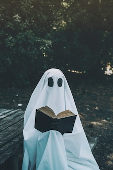 Human in ghost suit sitting on bench and reciting book