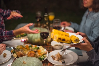 Human giving cooked corns to person at family dinner