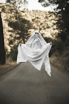 Human in gloomy ghost costume flying above countryside route