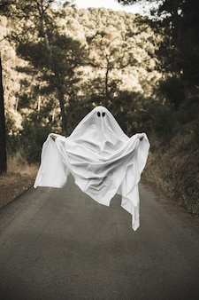 Human in gloomy ghost costume flying in countryside