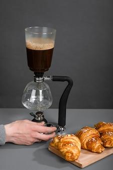 人間の手がコーヒーポットを調整して、灰色の壁のある部屋でドリップコーヒーを淹れます。