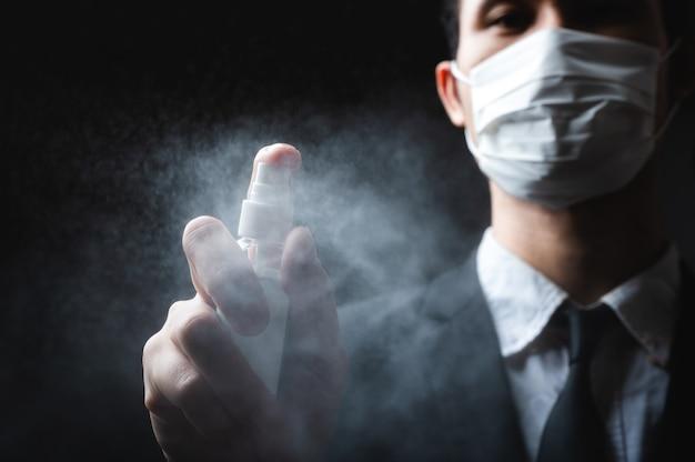 人間の手と暗い背景に防腐剤スプレーボトル。コロナウイルスの防疫対策。