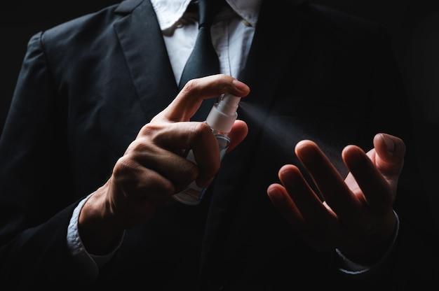 Human hand and antiseptic spray bottle on dark background. control epidemic prevention measures of coronavirus.