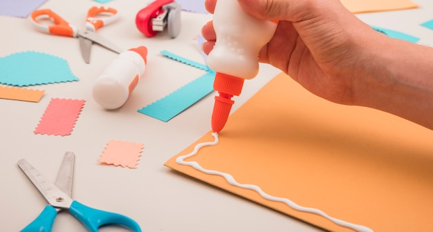 Human hand applying white glue on orange paper with scissor and stapler